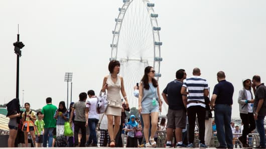 People walk near the Singapore Flyer in Singapore